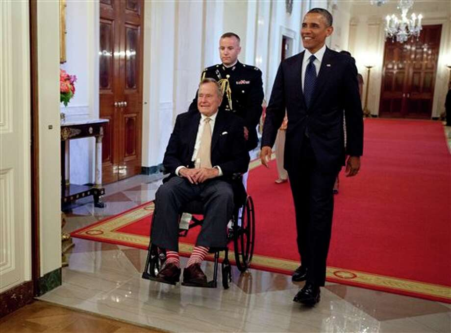 "President Barack Obama and former President George H. W. Bush arrive to present the 5,000th Daily Point of Light Award to Floyd Hammer and Kathy Hamilton, a retired couple and farm owners from Union, Iowa, in the East Room of the White House in Washington, Monday, July 15, 2013. Obama welcomed Bush to the White House in a salute to public service and to the drive for volunteerism that the 41st president inspired with his ""thousand points of light"" initiative more than two decades ago. Photo: Carolyn Kaster, AP / AP"