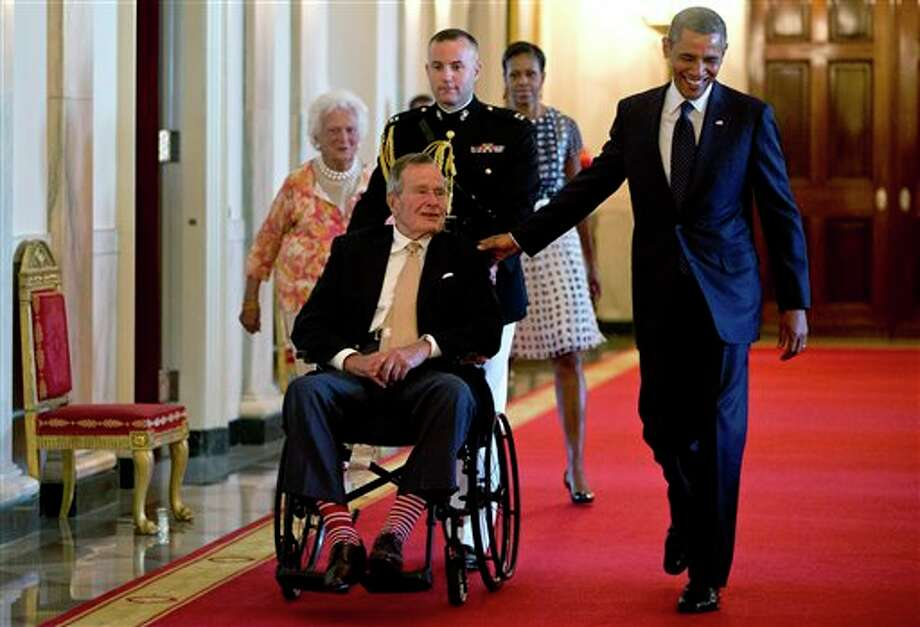 "President Barack Obama with former President George H. W. Bush, first lady Michelle Obama and former first lady Barbara Bush, behind left, arrive to present the 5,000th Daily Point of Light Award to Floyd Hammer and Kathy Hamilton, a retired couple and farm owners from Union, Iowa,  in the East Room of the White House in Washington, Monday, July 15, 2013. Obama welcomed Bush to the White House in a salute to public service and to the drive for volunteerism that the 41st president inspired with his ""thousand points of light"" initiative more than two decades ago. Photo: Carolyn Kaster, AP / AP"