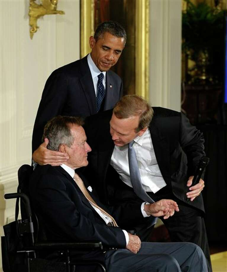 "President Barack Obama, standing, watches as former President George H. W. Bush, left, gets a hug from his son Neil Bush, during a ceremony to recognize the 5,000th Daily Point of Light Award in the East Room of the White House in Washington, Monday, July 15, 2013. Obama welcomed Bush to the White House in a salute to public service and to the drive for volunteerism that the 41st president inspired with his ""thousand points of light"" initiative more than two decades ago. Photo: Susan Walsh, AP / AP"