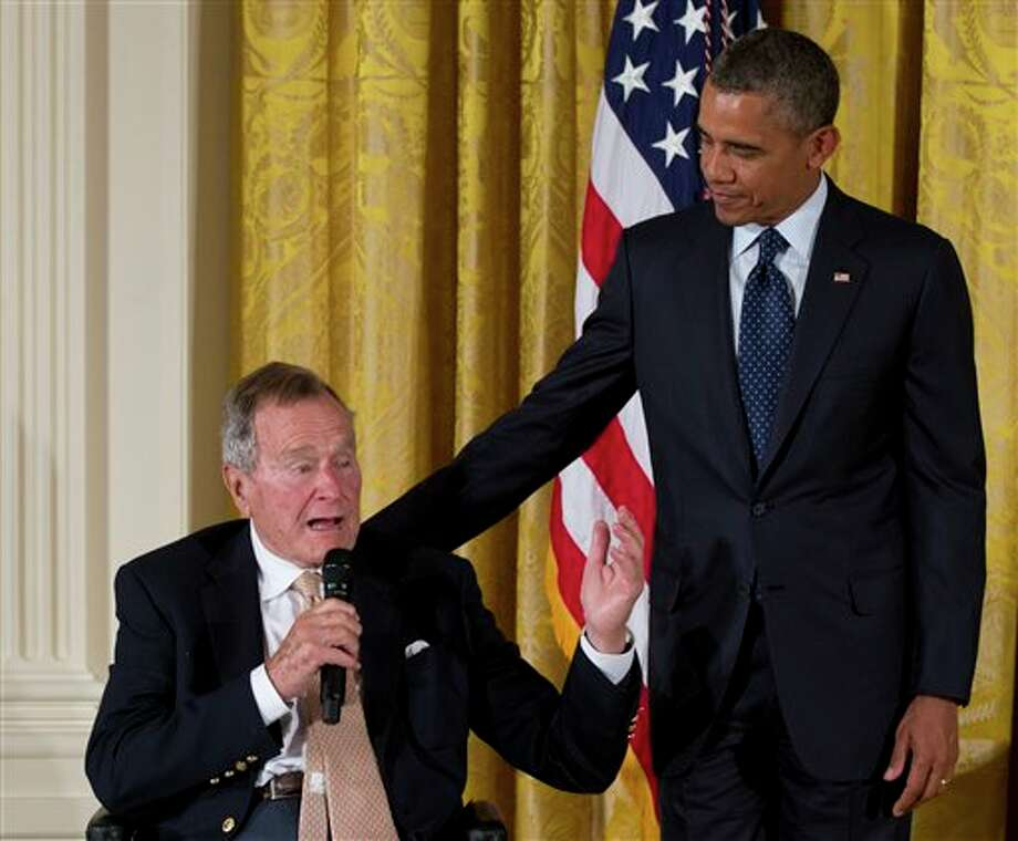 Former President George H. W. Bush speaks as President Barack Obama stands right, during a ceremony to  present the 5,000th Daily Point of Light Award to Floyd Hammer and Kathy Hamilton, from Union, Iowa, in the East Room of the White House in Washington, Monday, July 15, 2013. The 5,000th Daily Point of Light Award is the world's largest organization dedicated to volunteer service, mobilizing millions of people to take action that is changing the world and recognizes individuals who are making a difference through service and volunteerism. Photo: Carolyn Kaster, AP / AP