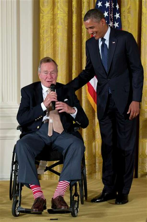 "Former President George H. W. Bush speaks as President Barack Obama stands right, as they participated in a ceremony to  present the 5,000th Daily Point of Light Award to Floyd Hammer and Kathy Hamilton, from Union, Iowa, in the East Room of the White House in Washington, Monday, July 15, 2013. Obama welcomed Bush to the White House in a salute to public service and to the drive for volunteerism that the 41st president inspired with his ""thousand points of light"" initiative more than two decades ago. Photo: Carolyn Kaster, AP / AP"