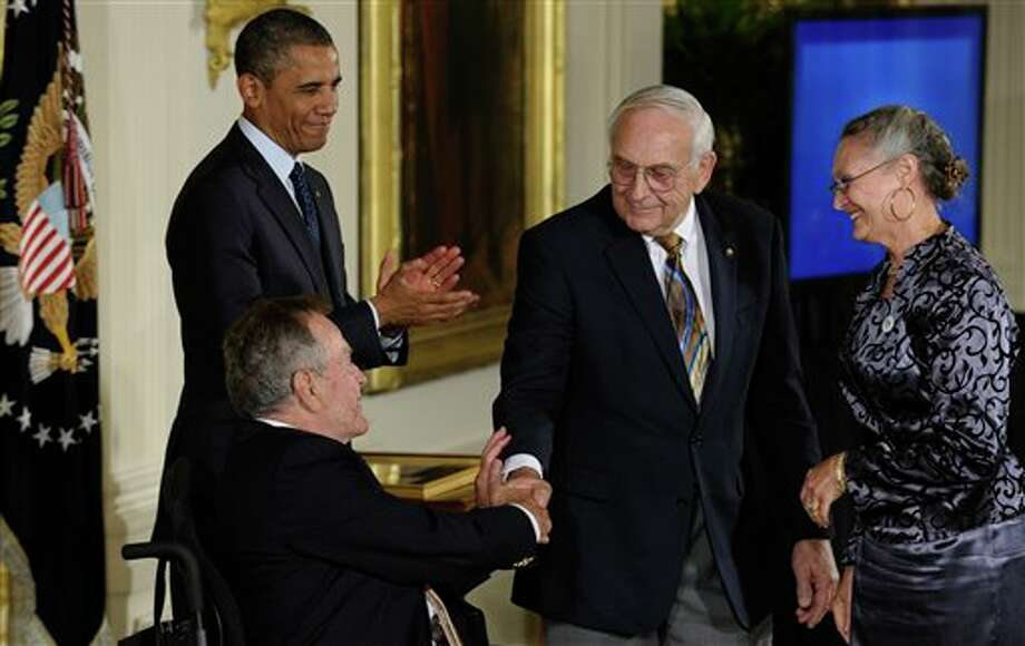 "President Barack Obama, rear left, watches as former President George H. W. Bush, seated, shakes hands with Floyd Hammer and Kathy Hamilton, a retired couple and farm owners from Union, Iowa, who were awarded with the 5,000th Daily Point of Light Award during a ceremony in the East Room of the White House in Washington, Monday, July 15, 2013. Obama welcomed Bush to the White House in a salute to public service and to the drive for volunteerism that the 41st president inspired with his ""thousand points of light"" initiative more than two decades ago. Photo: Susan Walsh, AP / AP"