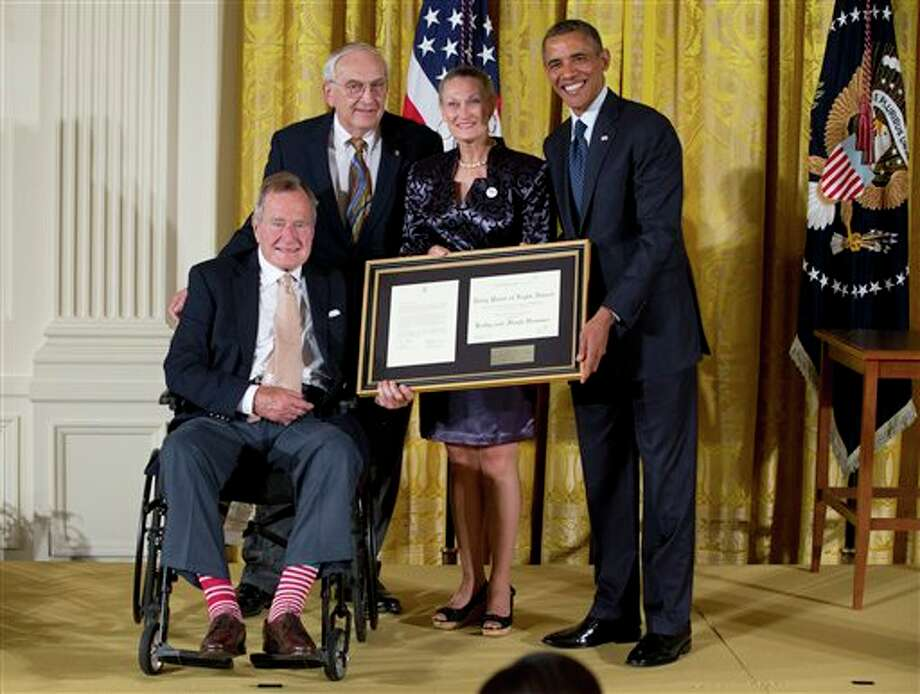 "President Barack Obama with former President George H. W. Bush, presents the 5,000th Daily Point of Light Award to Floyd Hammer and Kathy Hamilton, center, a retired couple and farm owners from Union, Iowa, in the East Room of the White House in Washington, Monday, July 15, 2013. Obama welcomed Bush to the White House in a salute to public service and to the drive for volunteerism that the 41st president inspired with his ""thousand points of light"" initiative more than two decades ago. Photo: Carolyn Kaster, AP / AP"