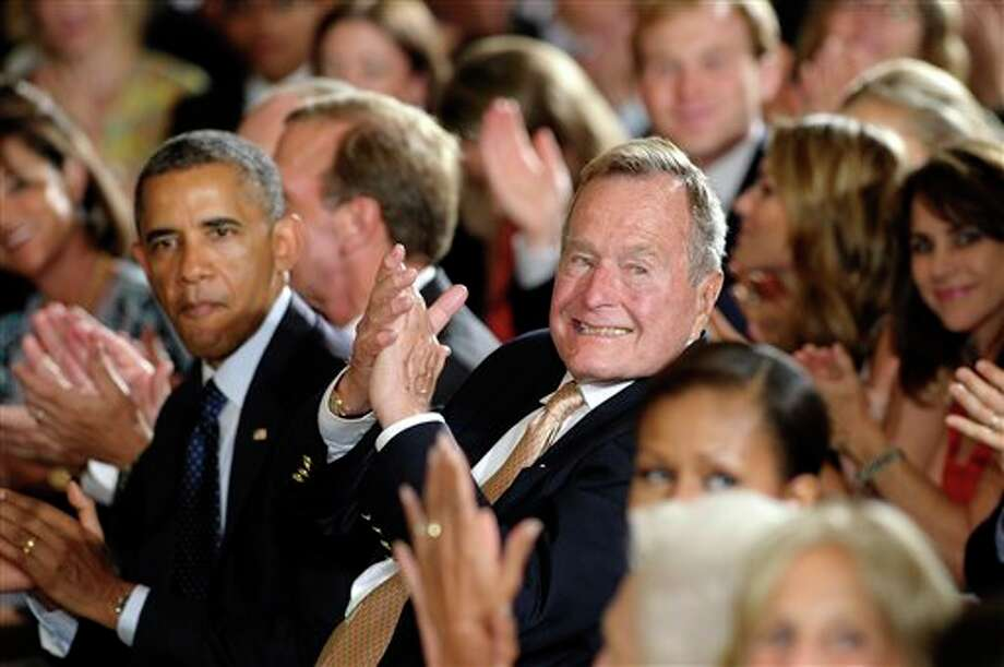 "Former President George H. W. Bush sitting next to President Barack Obama, left, recognizes a member of the audience after presenting the 5,000th Daily Point of Light Award in the East Room of the White House of the White House in Washington, Monday, July 15, 2013. Obama welcomed Bush to the White House in a salute to public service and to the drive for volunteerism that the 41st president inspired with his ""thousand points of light"" initiative more than two decades ago. Photo: Susan Walsh, AP / AP"