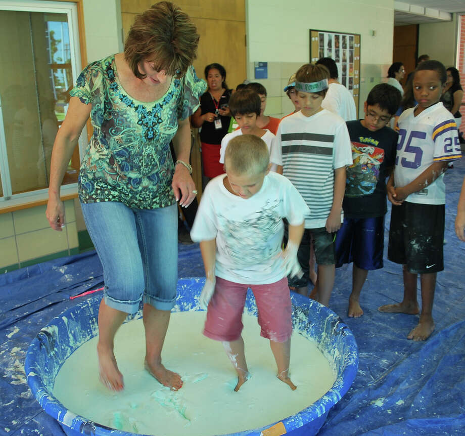 Brenda Hellyer, San Jacinto College chancellor, and her grandson, Zane Hellyer, jog on the surface of non-Newtonian fluid, created with a mixture of cornstarch and water. Photo: Photo Courtesy Of San Jacinto College