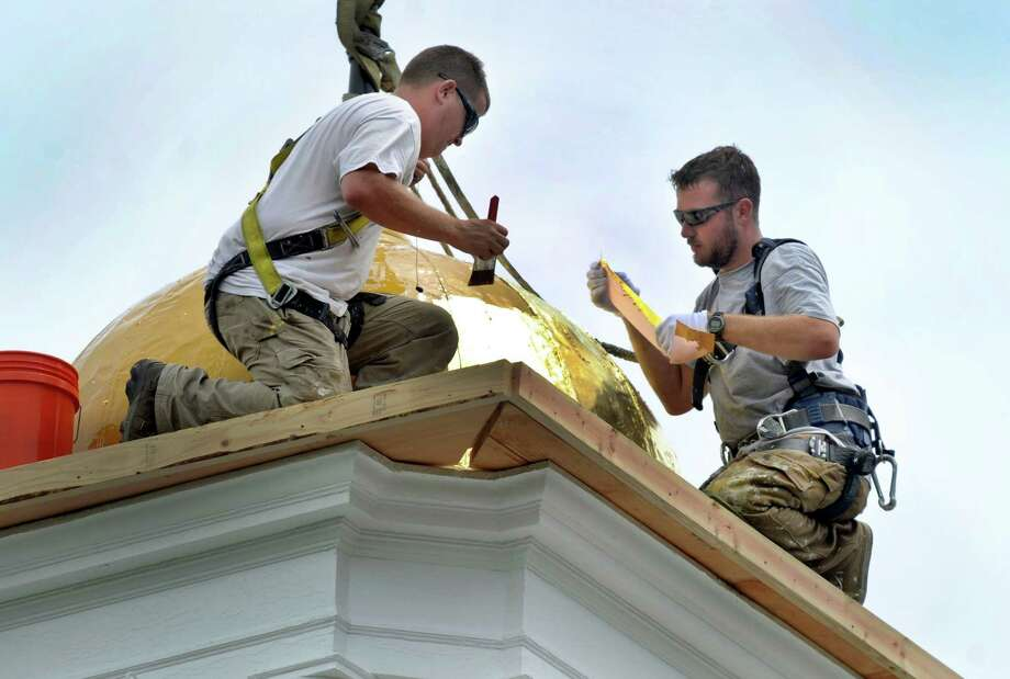 Paul Bastiaanse, left, and Dan Smith, guilders with Valley Restoration LLC of Torrington, Conn., do gilding work on the cupola at the Edmond Town Hall in Newtown, Conn., Wednesday, July 10, 2013. Photo: Carol Kaliff / The News-Times
