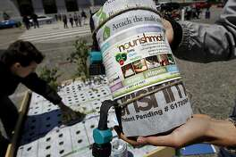 Phil Weiner holds the Nourishmat kit at the Civic Center Wednesday July 10, 2013. A new grow your own garden product called nourishmat is being demonstated in San Francisco, Calif. The kit comes with seed balls and and an irrigation hookup for your hose to grow veggies in tight, urban spaces.