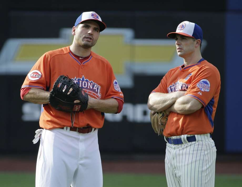 National League's David Wright, of the New York Mets, right, and Joey Votto of the Cincinnati Reds talk on the field during batting practice.