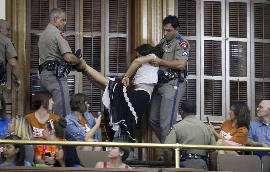 DPS troopers arrest a woman in the Senate chamber Photo: Jay Janner, Associated Press, Statesman.com