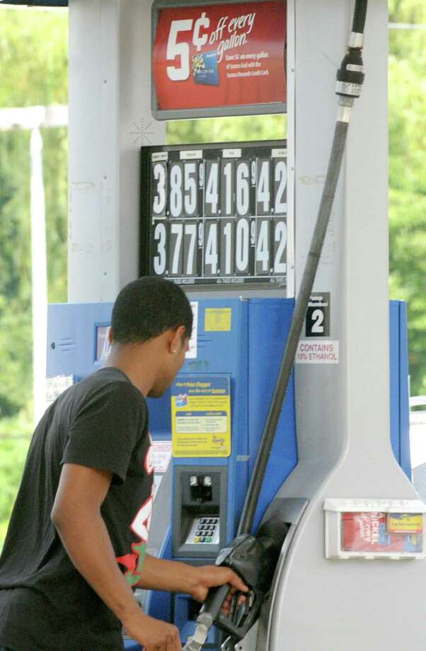 A young man puts the handle back after pumping gas for $3.85 a gallon Monday afternoon, July 15, 2013, at a Sunoco station on State St.  in Niskayuna, N.Y.  (Lori Van Buren / Times Union) Photo: Lori Van Buren / 00023170A