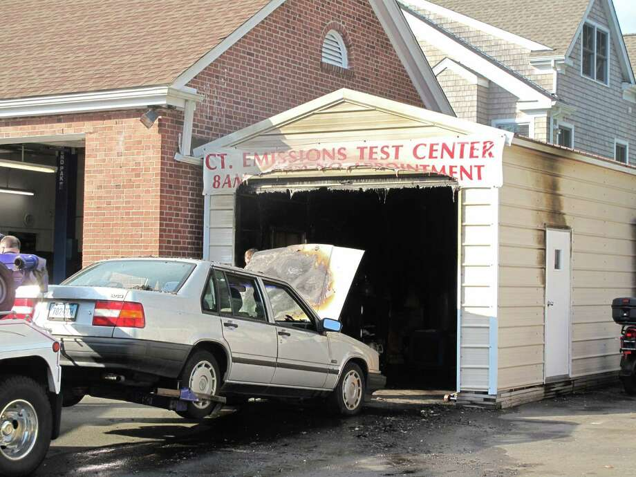 A gray Volvo sedan caught fire Monday and ignited a blaze inside the emissions testing bay at AC Auto Body at 182 Main St., New Canaan. The fire was contained to the bay and no one was injured. Photo: Tyler Woods