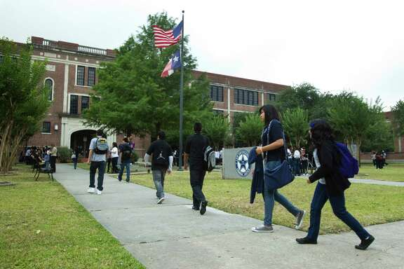 Students arrive to the High School for Law Enforcement and Criminal Justice Wednesday, May 25, 2011, in Houston. Houston ISD is proposing to change the start and end times of schools -- to better coordinate bus schedules and save about $1.2 million. The proposal means most high schools would have to start at 7:45 a.m. That will be a big change for students at several schools, including those at the High School for Law Enforcement and Criminal Justice, which now starts at 8:30 a.m.