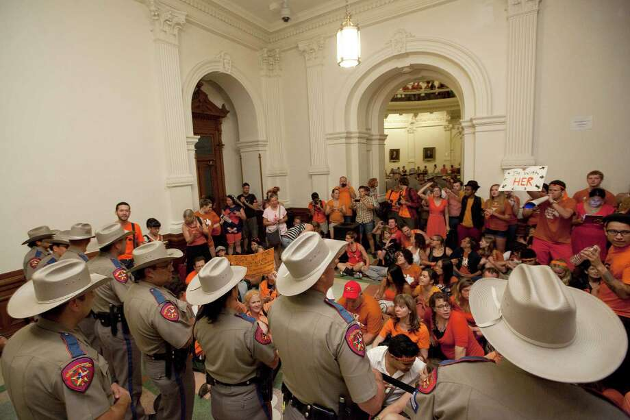 Abortion rights advocates protest HB2 from the area outside of the Senate Chamber in the State Capitol in Austin, Texas on Friday night, July 12, 2013.  Republicans in the Texas Legislature passed an omnibus abortion bill that is one of the most restrictive in the nation, but Democrats vowed Saturday to fight in the courts and at the ballot box as they used the measure to rally their supporters. More than 2,000 demonstrators filled the Capitol building in Austin to voice their opposition to the bill, including six protesters who were dragged out of the Senate chamber by state troopers for trying to disrupt the debate. The Republican majority passed the bill unchanged just before midnight, with all but one Democrat voting against it. (AP Photo/Tamir Kalifa) Photo: Tamir Kalifa, FRE / FR170773 AP