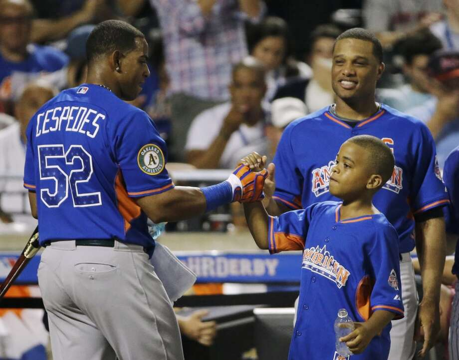 American League's Yoenis Cespedes is greeted by unidentified child and American League captain Robinson Cano.