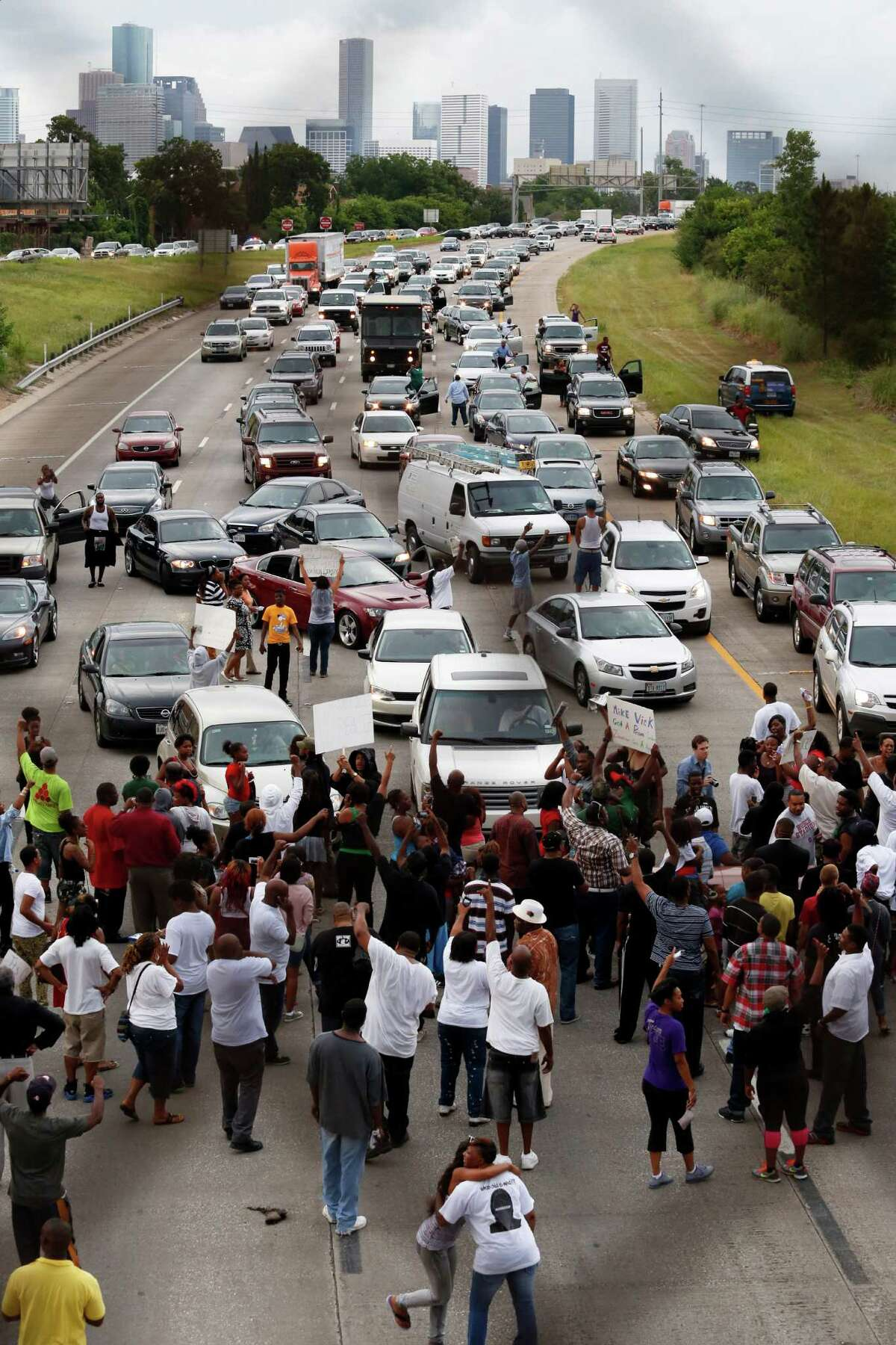 Protesters stop traffic on Texas 288 Monday, above, as activist Quanell X, at right, and local community leaders and hip-hop stars lead a protest that began at the Byrd Funeral Home on Wheeler.