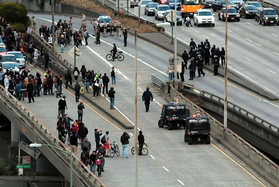 Protesters disrupt traffic on I-880 above Webster Street in Oakland during the third night of protests of the not-guilty verdict in Trayvon Martin's killing. Photo: Tamara De Jong