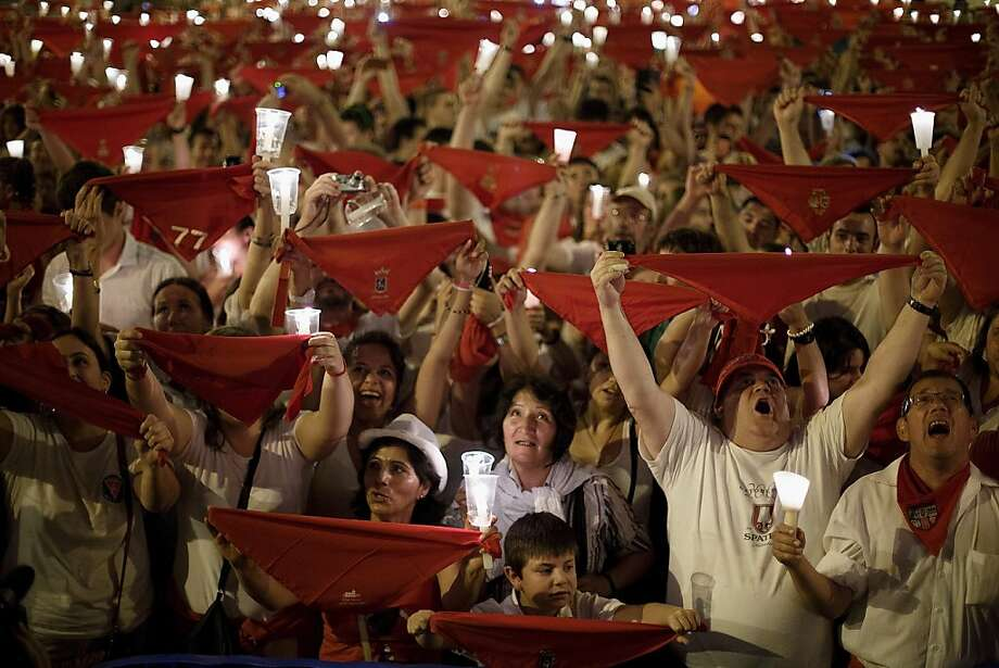 PAMPLONA, SPAIN - JULY 15:  Revellers raise their scarves and candles as they sing the 'Pobre de Mi' song, marking the end of the San Fermin festival on July 15, 2013 in Pamplona, Spain. The annual Fiesta de San Fermin, made famous by the 1926 novel of US writer Ernest Hemmingway 'The Sun Also Rises', involves the running of the bulls through the historic heart of Pamplona, this year for nine days from July 6-14.  (Photo by Pablo Blazquez Dominguez/Getty Images) *** BESTPIX *** Photo: Pablo Blazquez Dominguez, Getty Images