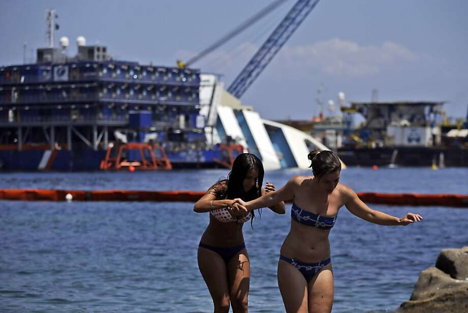 Sunbathers walk on rocks as the Costa Concordia cruiser is visible in background, in the Tuscan Island of Isola del Giglio, Monday, July 15, 2013. Salvage crews are working against time to right and remove the shipwrecked Costa Concordia cruise ship, which is steadily compressing down on itself from sheer weight onto its granite seabed perch off the Tuscan island of Giglio. Salvage master Nick Sloane said Monday that the Concordia has compressed some 3 meters (10 feet) since it came to rest on the rocks Jan. 13, 2012 after ramming a jagged reef during a stunt ordered by the captain that cost the lives of 32 people. (AP Photo/Gregorio Borgia) Photo: Gregorio Borgia, Associated Press