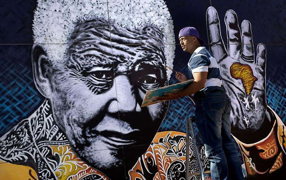South African artist John Adams works on a giant acrylic-on-canvas painting of Nelson Mandela in the driveway of his house in a suburb of Johannesburg, South Africa, Monday, July 15, 2013. Adams said he felt driven to create the painting as thanks to Mandela for creating educational opportunities that enabled him to become an artist, and plans to auction the painting, the proceeds of which will fund children's charities. (AP Photo/Ben Curtis) Photo: Ben Curtis, Associated Press