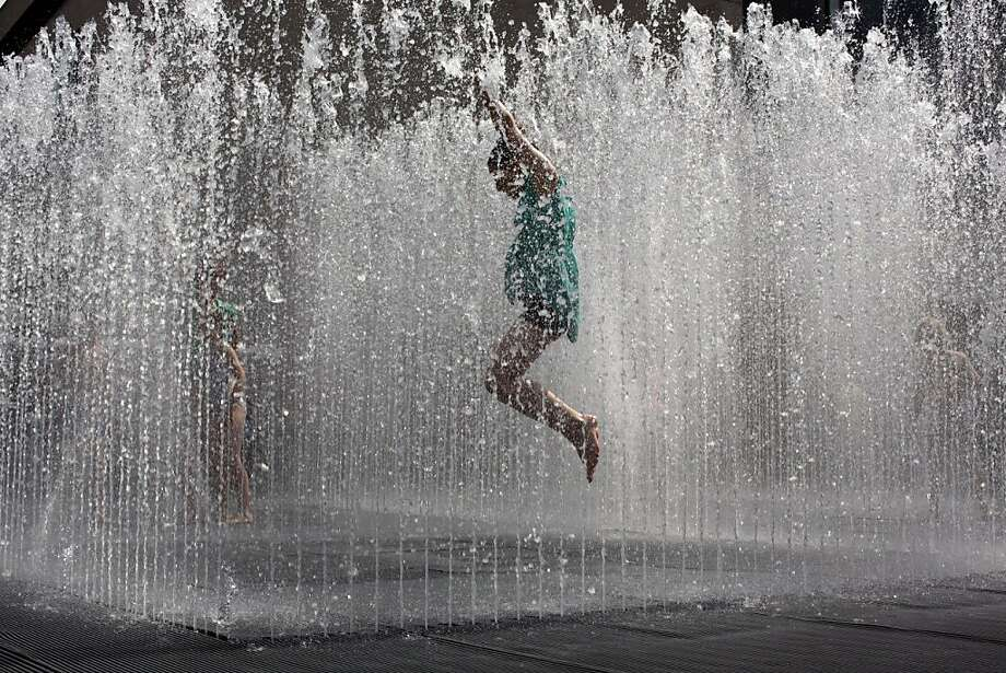 A youngster jumps in the midst of a fountain on the southbank of the River Thames in London, Monday, July 15, 2013. Temperatures reached 28 degrees Celsius (82 degrees Fahrenheit) in London on Monday. (AP Photo/Matt Dunham) Photo: Matt Dunham, Associated Press
