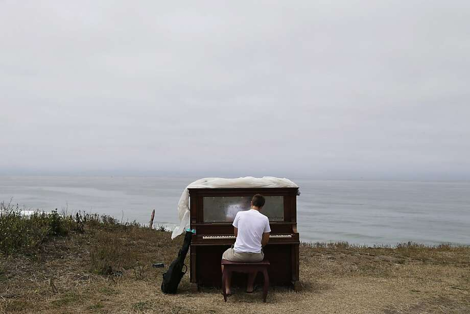 "Music student Dylan Gibbs, of Simsbury, Conn., plays a piano rested on a bluff at Poplar State Beach in Half Moon Bay., Calif., Monday, July 15, 2013. Twelve  pianos were strategically placed along various locations along the San Mateo County coastline as part of an art project entitled ""Opus Two for Twelve Pianos"" by area artist Mauro Ffortissimo. Ffortissimo and supporters have also been staging sunset piano recitals along the coast and inviting visitors to play the pianos. (AP Photo/Marcio Jose Sanchez) Photo: Marcio Jose Sanchez, Associated Press"