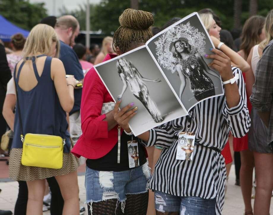"""Beyoncé fans flip through the official program of """"The Mrs. Carter Show World Tour."""" Photo: Michael Starghill Jr., Chronicle"""