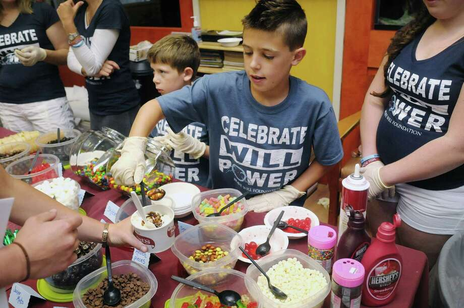 Brothers, Max, left, 6, and Ben Hladun, 9, scoop out toppings for hospital staff during an ice cream social to honor their younger brother during the Brave Will Foundation event at The Children's Hospital at Albany Medical Center on Monday, July 15, 2013, in Albany, N.Y.  The Brave Will Foundation with donations from Stewart's Shops held the event to mark Will Hladun's birthday, which was July 14th.  Will Hladun passed away in 2009 of a rare cancer at six months old.  Will's parents started the foundation that promotes the benefits of palliative care and programs which provide comprehensive care for infants and children experiencing a debilitating or life threatening medical condition.  The foundation donated $50,000 on Monday to the hospital to support the Journeys Palliative Care Program.  To date the foundation has donated $125,000.  The foundation also pledged $100,000 towards a dedicated palliative care room at the hospital that will be completed next year.     (Paul Buckowski / Times Union) Photo: Paul Buckowski / 00023154A