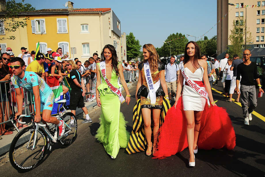 Miss Dauphine 2012, Miss Rhone Alpes 2012 and Miss Rhone 2013 walk amongst the riders before the start of stage fifteen of the 2013 Tour de France, a 242.5KM road stage from Givors to Mont Ventoux, on July 14, 2013 in Givors, France. Photo: Bryn Lennon, Getty Images / 2013 Getty Images