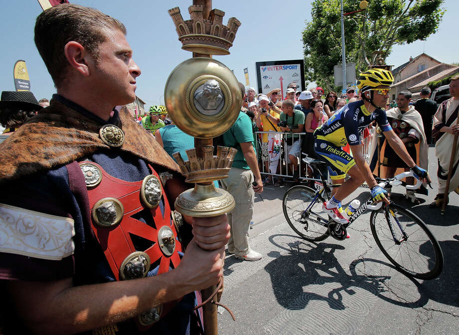 Spain's Alberto Contador passes a man dressed as a Roman gladiator prior to the sixteenth stage of the Tour de France cycling race over 168 kilometers (105 miles) with start in in Vaison-la-Romaine and finish in Gap, France, Tuesday July 16, 2013. Photo: Christophe Ena, AP / AP