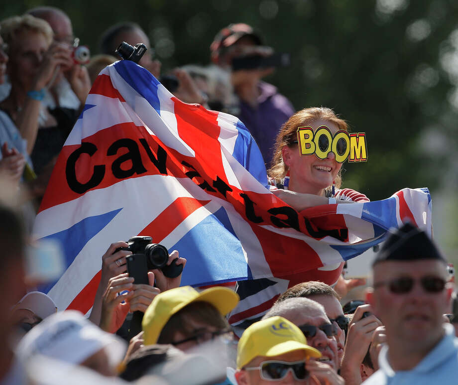 "A spectator holds a British flag reading ""Cav Attack"" referring to stage winner Mark Cavendish of Britain as he celebrates on the podium of the thirteenth stage of the Tour de France cycling race over 173 kilometers (108.1 miles) with start in in Tours and finish in Saint-Amand-Montrond, western France, Friday July 12 2013. Photo: Laurent Rebours, AP / AP"