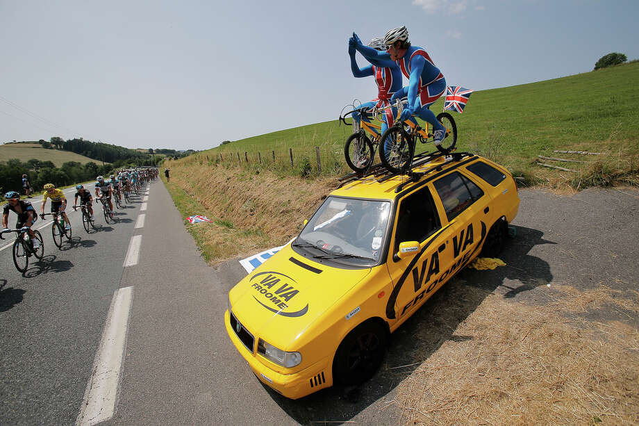 British fans cheers as Christopher Froome of Britain, wearing the overall leader's yellow jersey, left, passes with the pack during the fourteenth stage of the Tour de France cycling race over 191 kilometers (119.4 miles) with start in in Saint-Pourcain-sur-Sioule and finish in Lyon, central France, Saturday July 13 2013. Photo: Christophe Ena, ASSOCIATED PRESS / AP2013