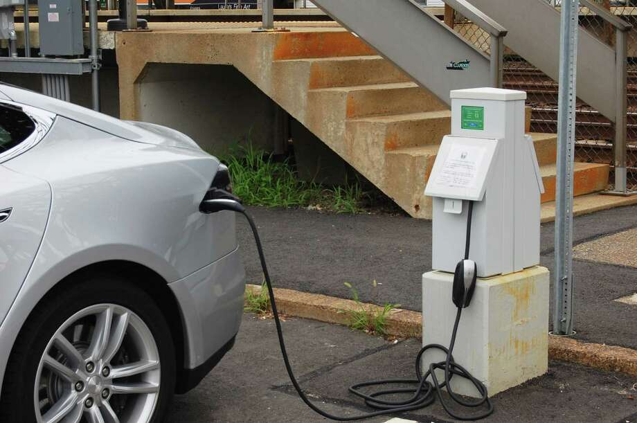 A Tesla electric car plugged into a charging station at the Saugatuck Train Station. Photo: Cameron Martin / Westport News