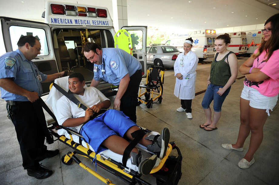 Brandon DeJesus, 13, of Bridgeport, is loaded on to a stretcher by EMTs Tim Mulligan, left, and Brian McIntyre, during a demonstration for students in the Summer Outreach Program camp at St. Vincent's College in Bridgeport, Conn on Tuesday, July 16, 2013. Photo: Brian A. Pounds / Connecticut Post