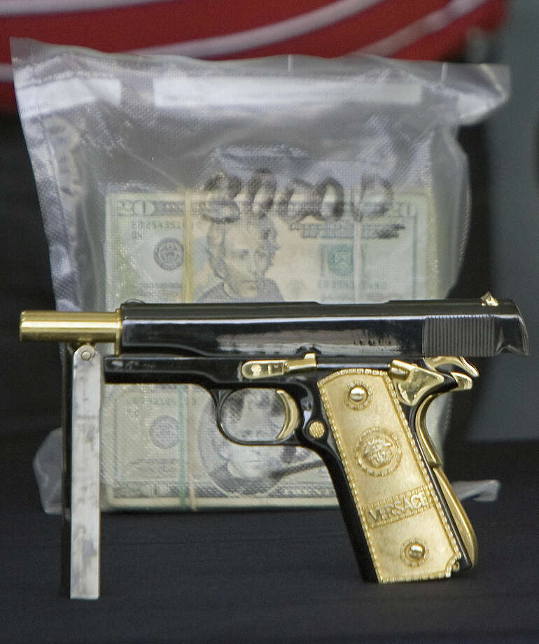 "The customized gold-plated handgun of Jaime Gonzalez Duran, a.k.a. ""Hummer"", founder of a group of hitmen called the ""Zetas"", shown to the press at the hangar of the Federal Police in Mexico City, on November 7, 2008. Gonzalez worked for drug trafficker Osiel Cardenas Guillen, a.k.a. ""El Mata Amigos"" (The Friends' Killer). Photo: ALFREDO ESTRELLA, AFP/Getty Images / 2008 AFP"