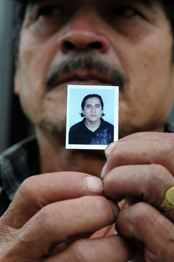 Honduran Miguel Angel Alvarado, shows a picture of his son twenty-seven-year-old Milton Alavarado Villanueva, one of the 72 migrants killed by a Mexican drug gang in Mexico, at the Foreign Ministry in Tegucigalpa on August 29, 2010 where he arrived to learn about the repatriation of the body of his body. The 72 people found bound, blindfolded and stacked against a wall inside a ranch warehouse on Tuesday in the northern town of San Fernando, were killed by the Zetas drug gang for refusing to work for them, according to the sole survivor of the massacre. Photo: ORLANDO SIERRA, AFP/Getty Images / 2010 AFP