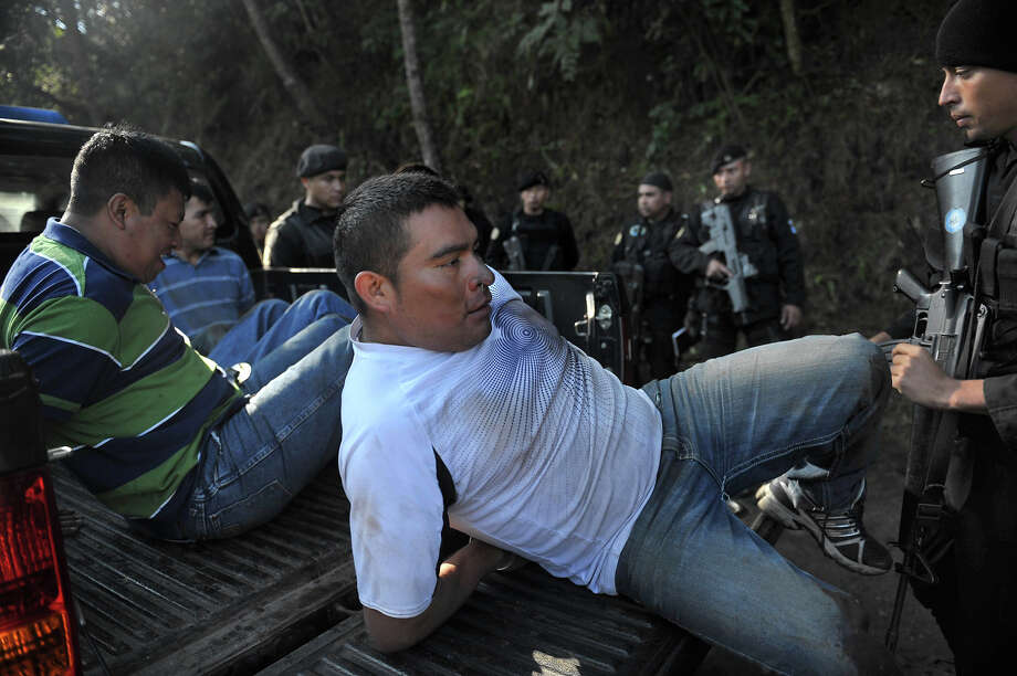 "Guatemalan police load onto a pickup four suspects allegedly belonging to ""los Zetas"" Mexican drug cartel after their arrest in Coban, Alta Verapaz, 220km north of Guatemala City, on December 20, 2010. Guatemala on Sunday launched a major new offensive against drug trafficking, with its territory heavily used as a transshipment point toward Mexico and the United States.  President Alvaro Colom announced measures including a local-area temporary suspension of some civil liberties such as the freedom to protest, and urged people to ""report criminals."" Photo: JOHAN ORDONEZ, AFP/Getty Images / 2010 AFP"