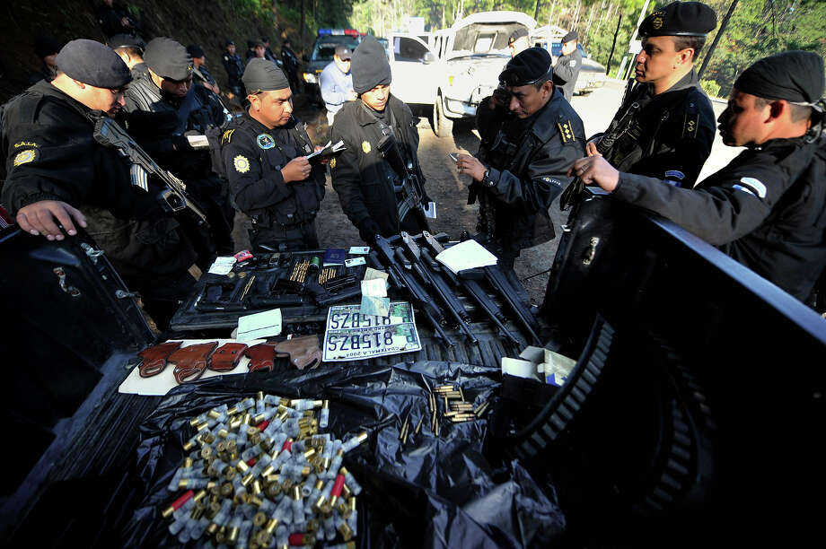 "Guatemalan police inspect the weapons and ammo seized to four suspects allegedly belonging to ""los Zetas"" Mexican drug cartel after their arrest in Coban, Alta Verapaz, 220km north of Guatemala City, on December 20, 2010. Guatemala on Sunday launched a major new offensive against drug trafficking, with its territory heavily used as a transshipment point toward Mexico and the United States.  President Alvaro Colom announced measures including a local-area temporary suspension of some civil liberties such as the freedom to protest, and urged people to ""report criminals."" Photo: JOHAN ORDONEZ, AFP/Getty Images / 2010 AFP"
