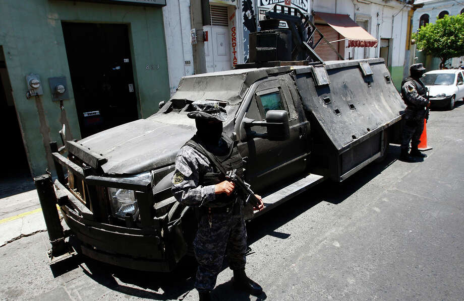 "Mexican policemen stand guard next to an armored car seized to alleged members of the Mexican drug cartel ""Los Zetas"" and presented to the press on May 23, 2011 in Guadalajara, Jalisco State. The armored car called ""The Z Monster"" has a capacity to transport about 20 men and has a turret to place a heavy machine gun. Photo: HECTOR GUERRERO, AFP/Getty Images / 2011 AFP"