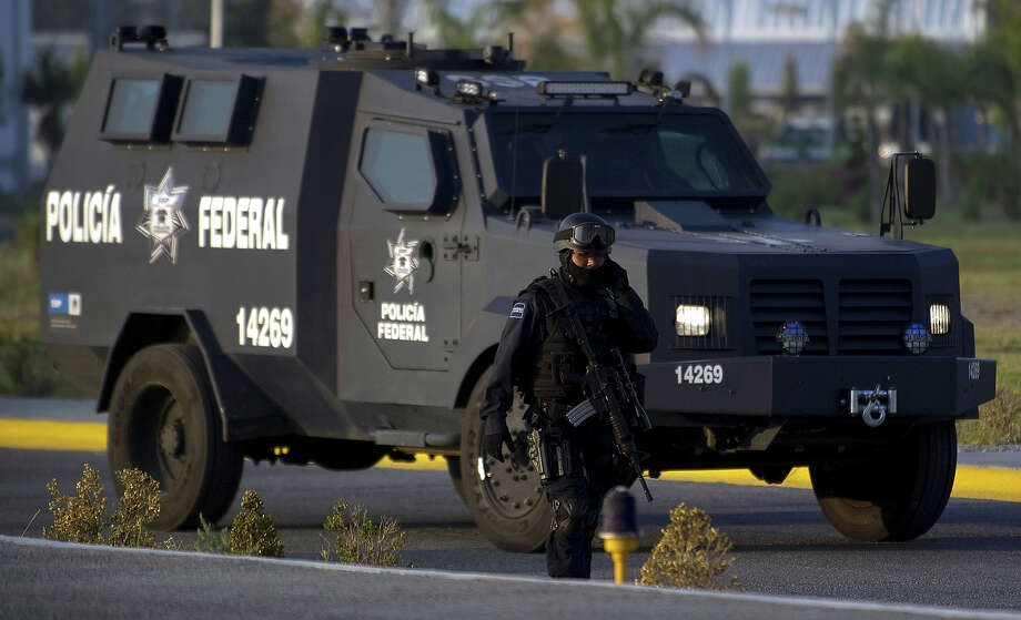 "A Federal policeman talks on his mobile phone as he escorts the armored car carrying the member of Los Zetas drug cartel Edgar Huerta Montiel, aka ""El Wache"", before his presentation to the press at the headquarter of Federal Police in Iztapalapa, on June 17, 2011. Huerta Montiel is accused of the kidnap of two truck with 70 Central American immigrants and to kill at least ten of them on August 2010, and having responsibility in the slaughter of more than 145 people found in mass graves in San Fernando, Tamaulipas. Photo: YURI CORTEZ, AFP/Getty Images / 2011 AFP"
