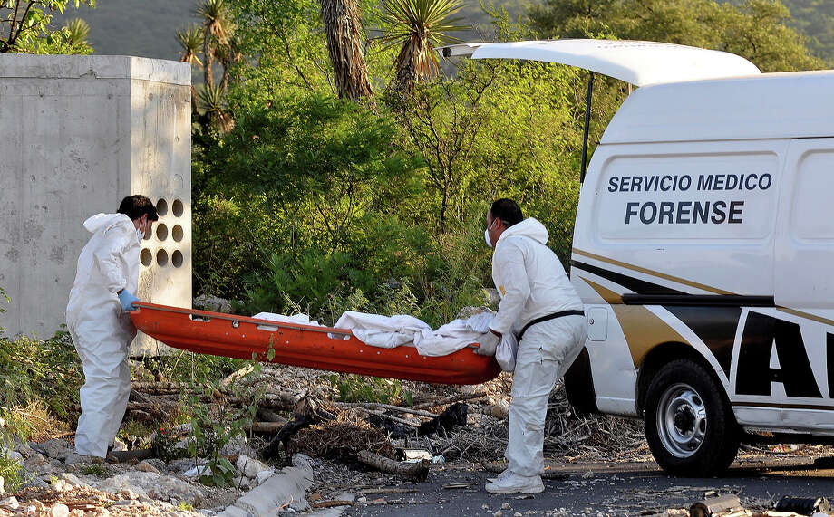 "Forensic personnel remove a body found in a clandestine trench in Monterrey city, Mexico on August 30, 2011. Due the interrogation of detainees involved in the arson of the Casino Royale on August 25, police found a clandestine grave with the remains of a corpse, but said that ""there could be six more.""Monterrey, the third largest city in Mexico, is immersed in an escalation of violence since 2010 by the disputes between the Gulf Cartel and the Zetas, former allies who are fighting criminal activity. Photo: AFP, AFP/Getty Images / 2011 AFP"