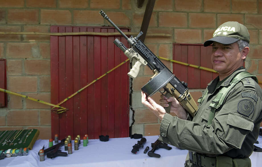 "Colombian police director Jose Roberto Leon Riano (L) shows a 5.56 FN Herstal assault rifle seized in the house where Erikson Vargas, a.k.a. Sebastian, alleged drug gang leader of ""La Oficina de Envigado"" was captured early this week, near Medellin (northeast), in Girardota municipality, Antioquia department, Colombia, on August 9, 2012. Sebastian, who took command of the drug gang after the arrest of Maximiliano Bonilla - a.k.a. Valenciano - in Venezuela last November, and is pointed to maintain alliances with Mexican cartel ""Los Zetas"" will be extradited to the US, Colombian President Juan Manuel Santos said. Photo: RAUL ARBOLEDA, AFP/Getty Images / 2012 AFP"