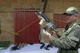 """Colombian police director Jose Roberto Leon Riano (L) shows a 5.56 FN Herstal assault rifle seized in the house where Erikson Vargas, a.k.a. Sebastian, alleged drug gang leader of """"La Oficina de Envigado"""" was captured early this week, near Medellin (northeast), in Girardota municipality, Antioquia department, Colombia, on August 9, 2012. Sebastian, who took command of the drug gang after the arrest of Maximiliano Bonilla - a.k.a. Valenciano - in Venezuela last November, and is pointed to maintain alliances with Mexican cartel """"Los Zetas"""" will be extradited to the US, Colombian President Juan Manuel Santos said."""