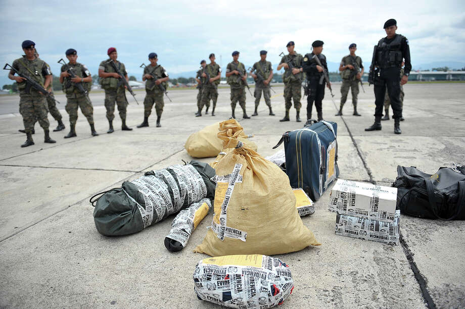 Members of the National Civil Police and the Guatemalan Army guard weapons and other evidence upon their arrival to a Guatemalan Air Force base in Guatemala City on June 5, 2011. The weapons were found in Coban department, some 215 kms north of Guatemala City, when they detained alleged members of the Los Zetas Mexican drug cartel, which is accused of involvement in the murder of prosecutor Allan Stowlinsky, as well as 27 peasants in Peten department last May. Photo: JOHAN ORDONEZ, AFP/Getty Images / 2013 AFP