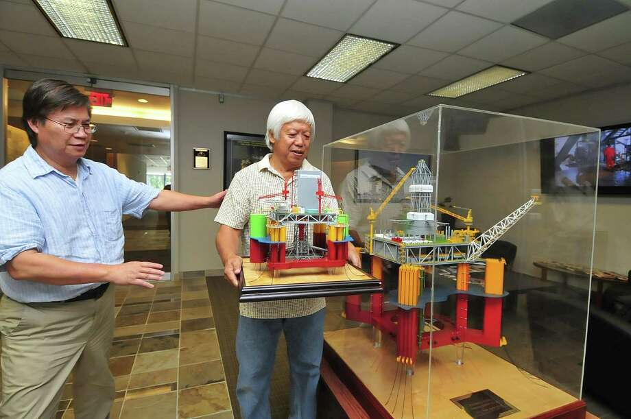 """Ngok Lai , left, manager of operations for Houston Offshore Engineering, guides Xiaodong Yan, Sugar Land model builder, as he holds a model of an offshore oil drilling platform created for Lockheed Martin. At right is a model of a """"Paired-Column Semisubmersible-Dry Tree Application"""" oil platform.    Ngok Lai , left, manager of operations for Houston Offshore Engineering, guides Xiaodong Yan, Sugar Land model builder, as he holds a model of an offshore oil drilling platform created for Lockheed Martin. At right is a model of a """"Paired-Column Semisubmersible-Dry Tree Application"""" oil platform. Photo: Â Tony Bullard 2013, Freelance Photographer / © Tony Bullard & the Houston Chronicle"""