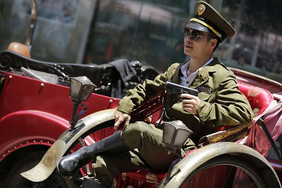 Mao's nemesis: A tourist poses as a Kuomintang, or Chinese Nationalist, army officer in Shanghai, a stunt that 40 years ago probably would have resulted in a trip to a re-education camp or worse. Photo: Eugene Hoshiko, Associated Press