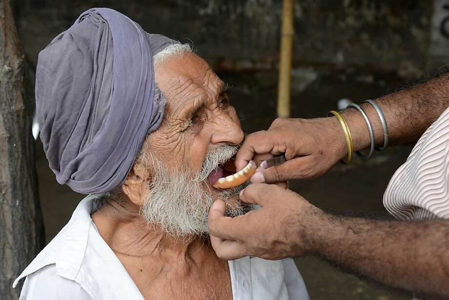 No appointment necessary: A roadside dentist fits dentures for Jagar Singh in Amritsar, India. Many street 