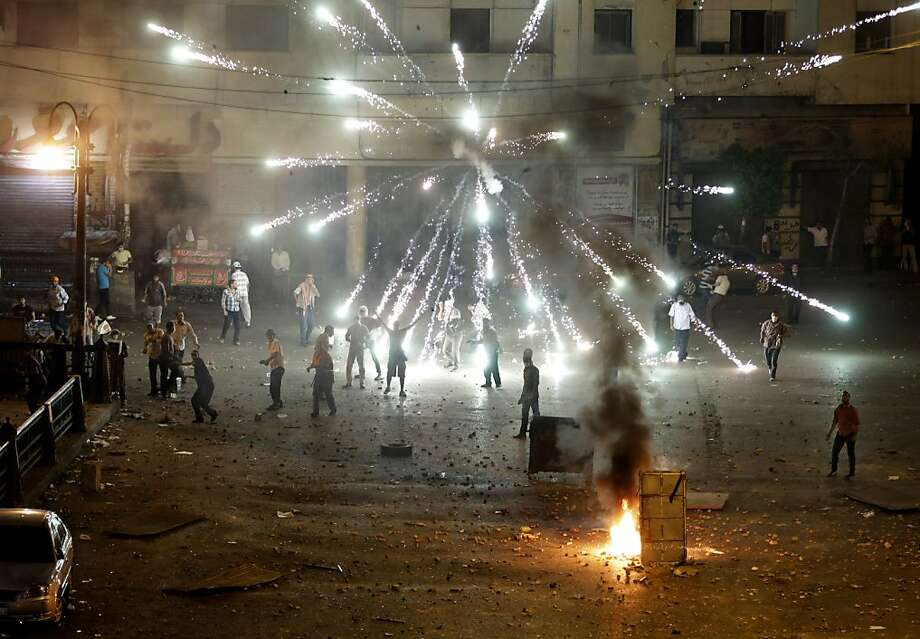 Egyptian demonstrators use pyrotechnics on foes:A firework fired by opponents of ousted President Mohammed Morsi explodes over his supporters during clashes in downtown Cairo. The pro-Morsi protesters, numbering in the thousands, burned tires, threw rocks and blocked traffic on a major city artery. Photo: Hussein Malla, Associated Press