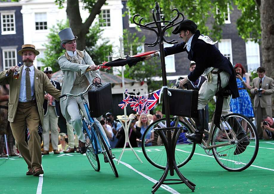 "Surely you joust: Foppish cyclists try to upend each other with bumbershoots during ""The Chap Olympiad,"" a lighthearted social sporting event aimed at revisiting the fashions of early 20th-century England (and even earlier apparently). Jolly good fun. Photo: Carl Court, AFP/Getty Images"