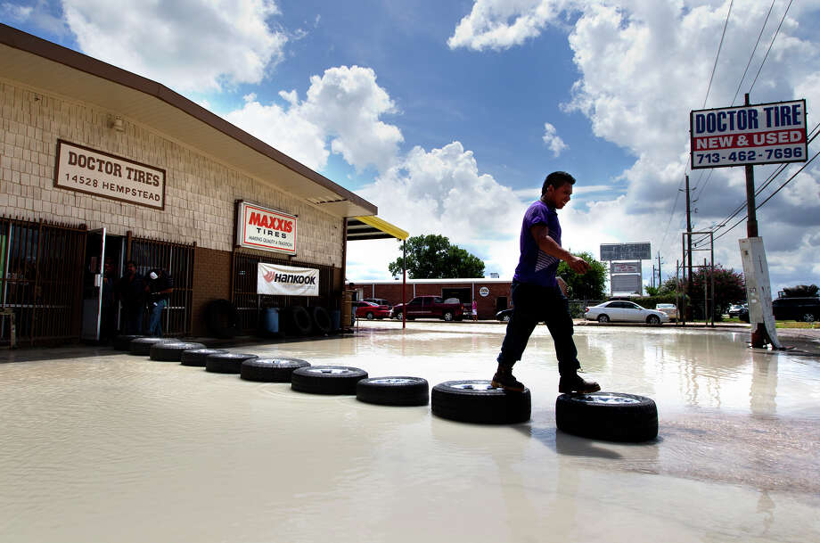Juan Martinez uses tires and wheels laid to make a dry path to cross a flooded area in front of Doctor Tire after a water main broke on Hempstead Highway near Gessner, Tuesday, July 16, 2013, in Houston. Photo: Cody Duty, Houston Chronicle / © 2013 Houston Chronicle