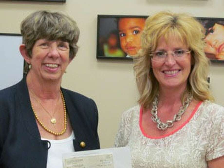 Nancy Ferriman, left, president of the Daughters of the King chapter at Good Shepherd Episcopal Church, Tomball, presents a check to Kelly Hamann of TOMAGWA to help with their work in providing quality health care to uninsured, low-income people. Photo: Contributed Photo